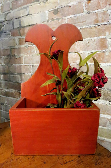 """Online, John & Kaye's """"Colonial Candlebox"""" is described and sold as, """"Distressed redish/orange with dark brown stain. Box measures 14""""h x 8.5"""" w x 4.75"""" d. Sorry does not include flower pick."""""""